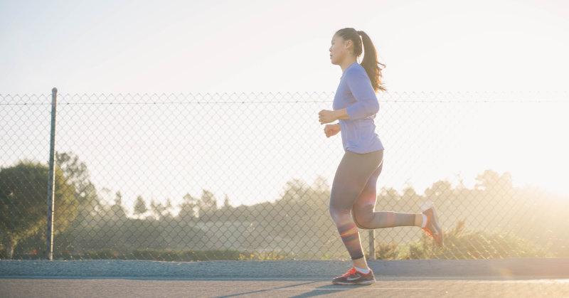 Frau die in warmen Sportklamotten in der Natur laufen ist