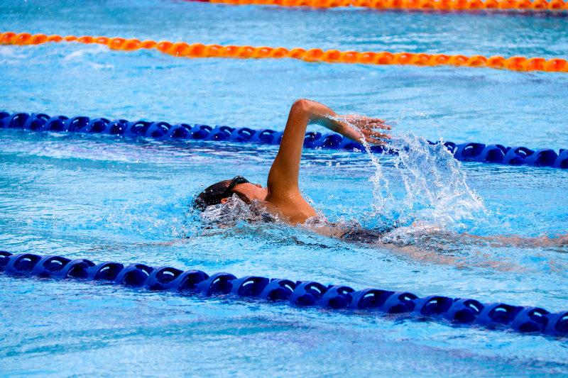 Person mit Schwimmbrille beim Kraulen, wie sie in einem Becken Bahnen zieht