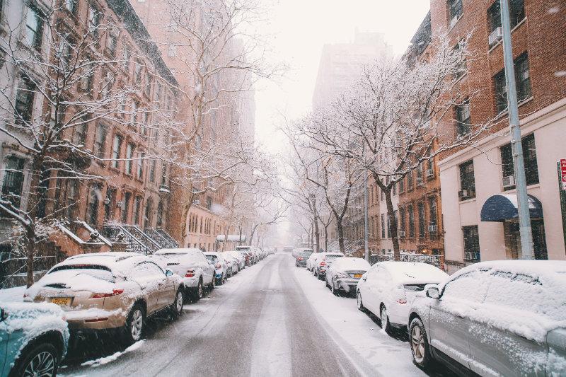 Eine zugeschneite Straße, auf der am Rand viele Autos geparkt sind