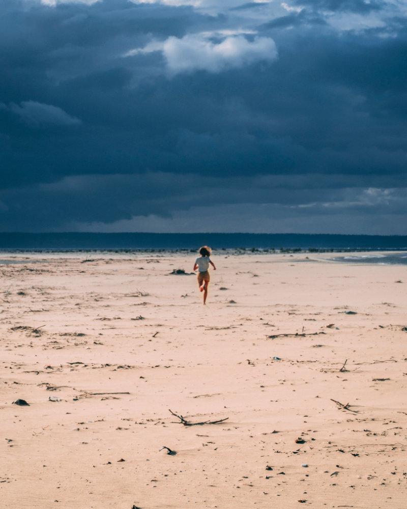 Ein Strand mit bewölktem Himmel auf dem in der Ferne eine Frau zu sehen ist die aufs Wasser zurennt
