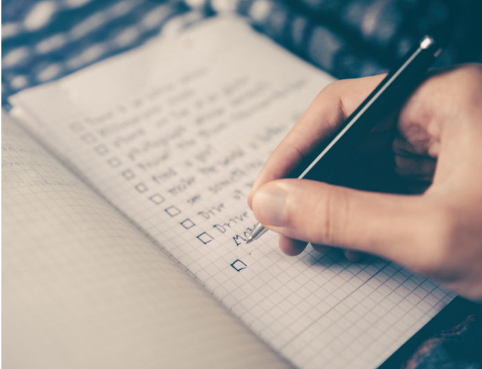 eine Hand die eine to Do Liste schreibt