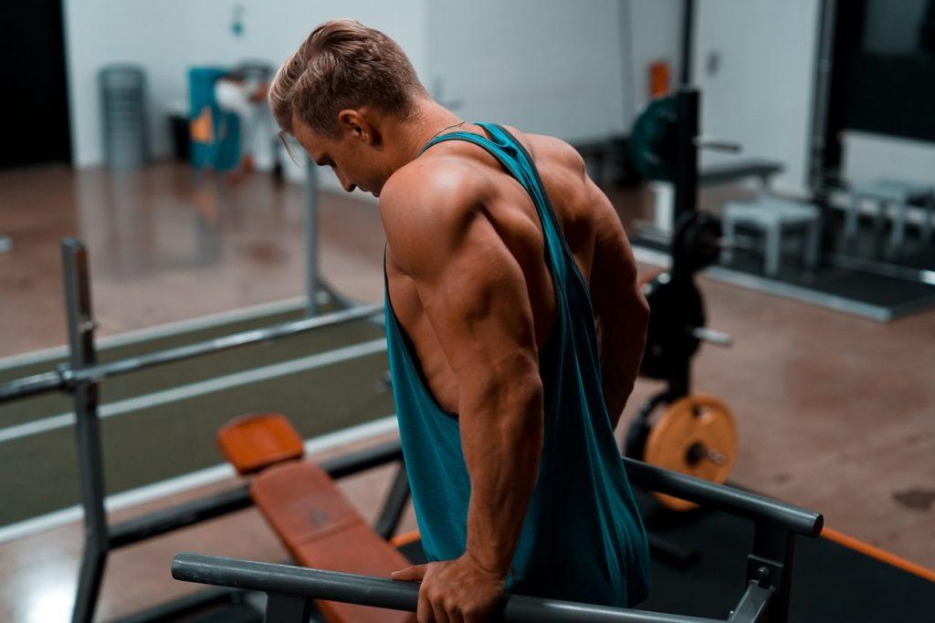 Ein muskolöser MAnn der im Fitnessstudio Gewichte hebt