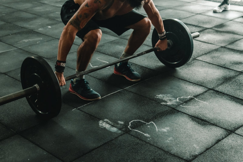 Bodybuilder der zu sehen ist, wie er ein Gewicht vom Boden aufhebt