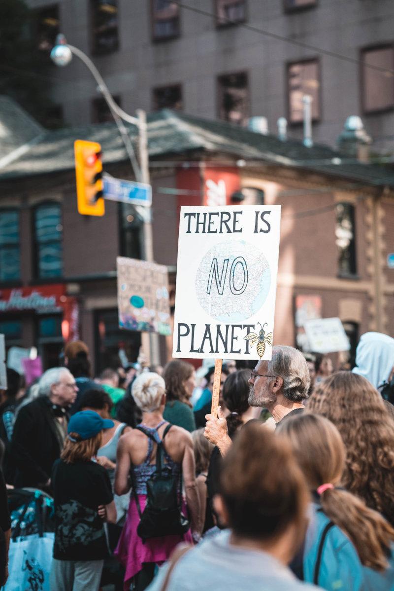 """Eine Demonstration, bei der ein Schild im Vordergrund ist, mit der Aufschrift: """"There is no Planet B"""""""